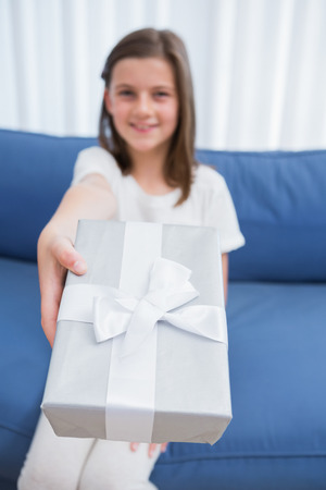 Little girl offering a silver gift at home in the living room