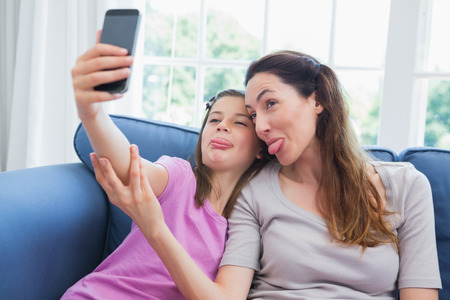 one child: Mother and daughter taking a selfie at home in the living room