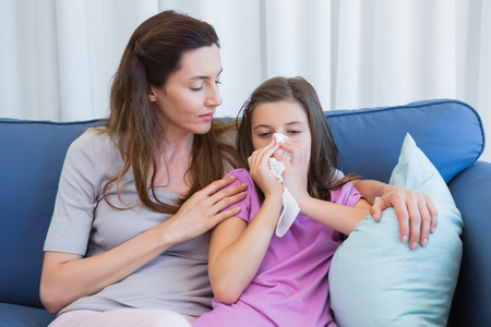 blowing nose: Mother helping daughter blow her nose at home in the living room