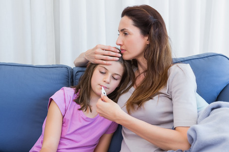 niños enfermos: Madre que toma temperatura de la hija enferma en casa, en la sala de estar