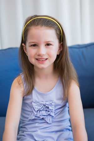 domicile: Little girl smiling at camera at home in the living room