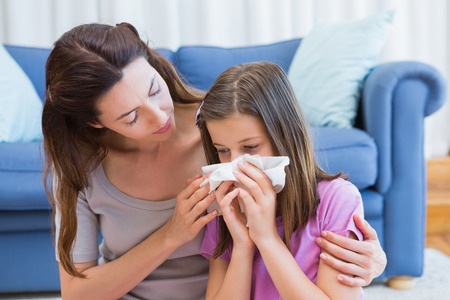 family with one child: Mother helping daughter blow her nose at home in the living room