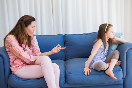 reprimanding: Mother scolding her naughty daughter at home in the living room Stock Photo