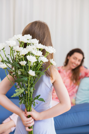 gift behind back: Daughter surprising mother with flowers at home in the living room