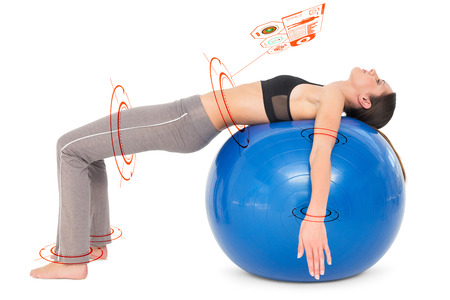ball stretching: Side view of a fit woman stretching on fitness ball against fitness interface