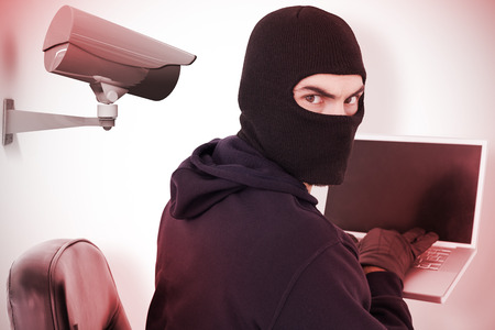Hacker sitting and hacking laptop  against cctv camera photo