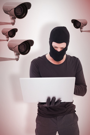 stolen identity: Hacker using laptop to steal identity against cctv camera