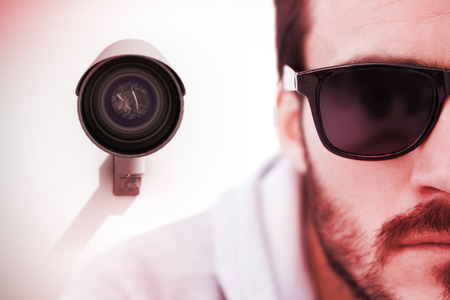 intimidating: Close up of serious man wearing sunglasses against cctv camera
