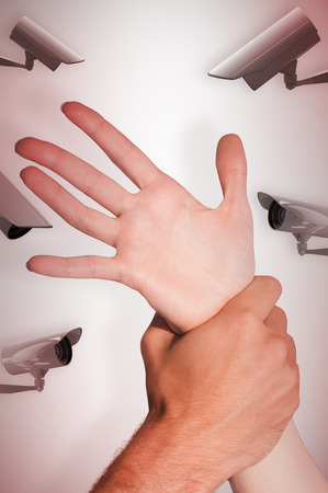 cowering: Womans wrist held by man against cctv camera Stock Photo