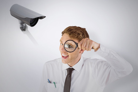 geeky: Geeky businessman looking through magnifying glass against cctv camera