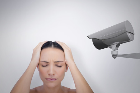 pounding head: Woman with headache against cctv camera Stock Photo