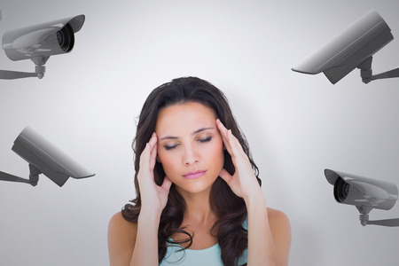 wincing: Pretty brunette with a headache against cctv camera