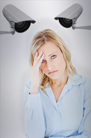 wincing: Woman with headache against cctv camera Stock Photo