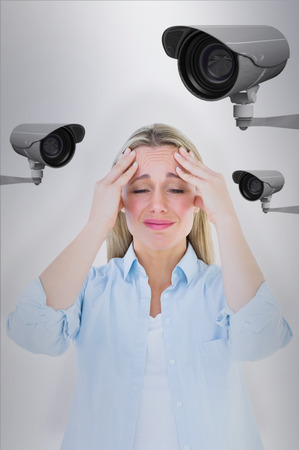 Portrait of a blonde getting a headache against cctv camera