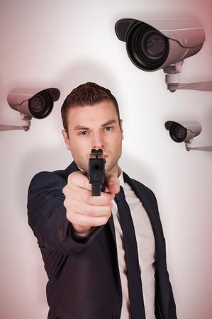 Serious businessman pointing a gun against cctv camera photo