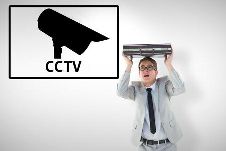 sheltering: Handsome businessman sheltering with briefcase against cctv