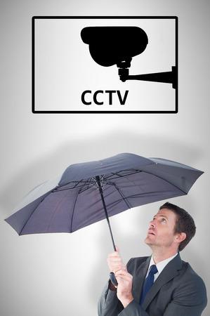sheltering: Businessman sheltering under black umbrella against cctv Stock Photo