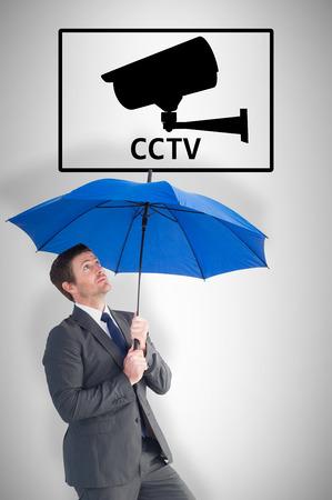 sheltering: Businessman sheltering under blue umbrella against cctv