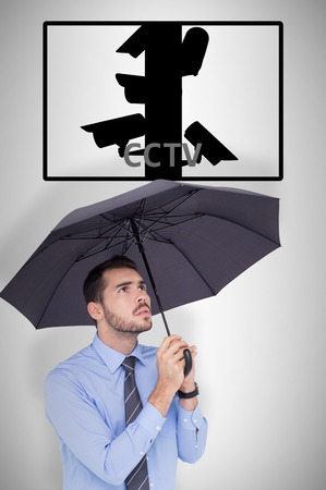 sheltering: Anxious businessman sheltering with umbrella  against cctv