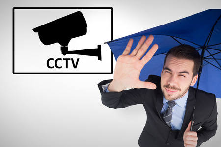 Blinded businessman protecting his eyes with his hand against cctv photo