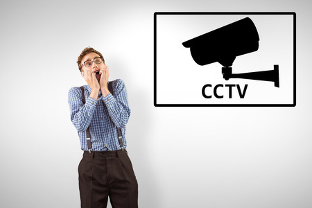geeky: Geeky hipster biting his nails against cctv Stock Photo