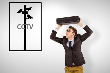 geeky: Young geeky businessman holding briefcase against cctv Stock Photo