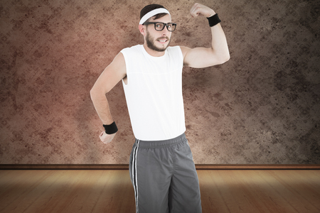 cheesy grin: Geeky hipster posing in sportswear against red background with vignette