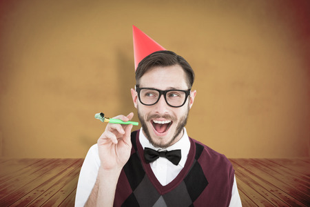 cheesy grin: Geeky hipster in party hat with horn against yellow background with vignette Stock Photo