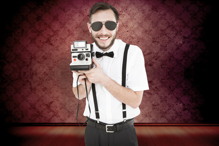 aviators: Geeky hipster holding a retro camera against purple vignette