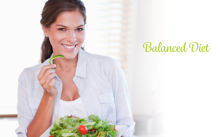 サラダを食べて笑顔の女性に対して単語のバランスの取れた食事