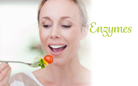 enzymes: The word enzymes against woman eating a tomato Stock Photo