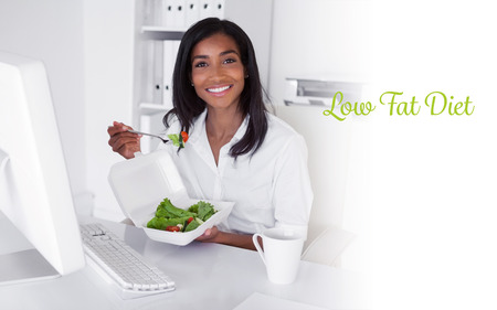 low fat diet: The word low fat diet against happy pretty businesswoman eating a salad at her desk