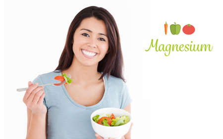 magnesium: The word magnesium against beautiful woman eating a bowl of salad Stock Photo