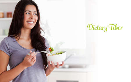 dietary fiber: The word dietary fiber against attractive woman enjoying a bowl of salad while standing