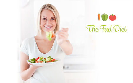 fad: The word the fad diet against close up of a good looking woman eating salad
