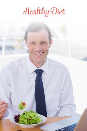 diet healthy: La dieta sana palabra contra hombre de negocios alegre comer una ensalada en su escritorio