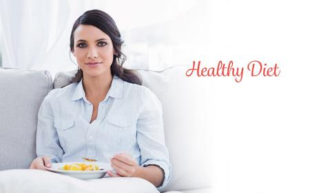diet healthy: La dieta sana palabra contra la mujer bonita que se sienta en el sof� comiendo ensalada de frutas