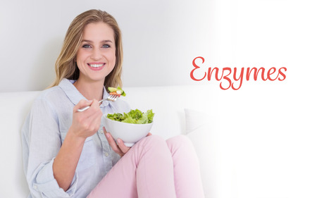 enzymes: The word enzymes against smiling casual blonde sitting on couch holding salad bowl