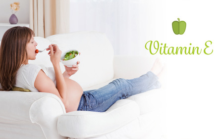 e pretty: The word vitamin e against pretty pregnant woman eating a salad while lying on a sofa