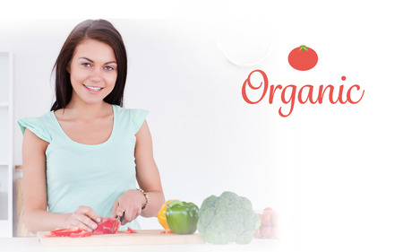 The word organic against woman slicing a pepper while looking at the camera photo
