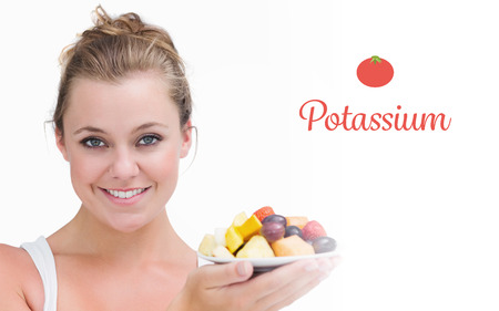 potassium: The word potassium against woman holding up a plate fruits Stock Photo