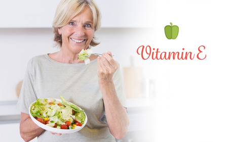 The word vitamin e against smiling woman eating salad photo