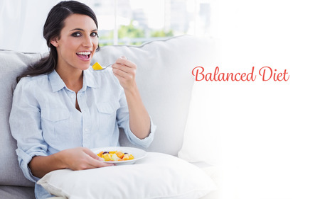 balanced diet: The word balanced diet against happy woman sitting on the sofa eating fruit salad Stock Photo