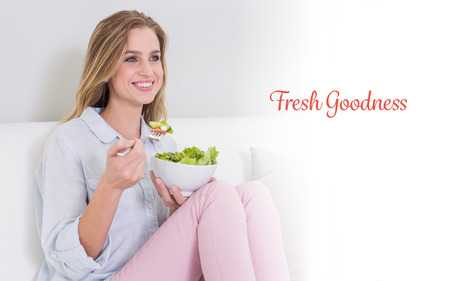 goodness: The word fresh goodness against happy casual blonde sitting on couch holding salad bowl Stock Photo