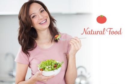 alimentacion natural: La palabra alimentos naturales contra el retrato de una mujer sonriente con un plato de ensalada en la cocina