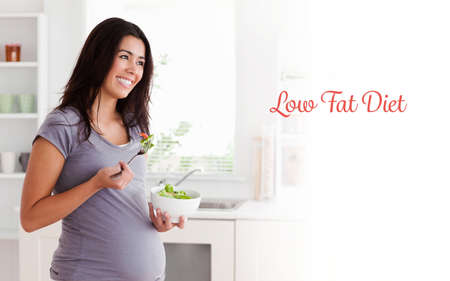 low fat diet: The word low fat diet against beautiful pregnant woman holding a bowl of salad while standing