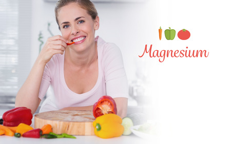 The word magnesium against cheerful woman eating vegetables