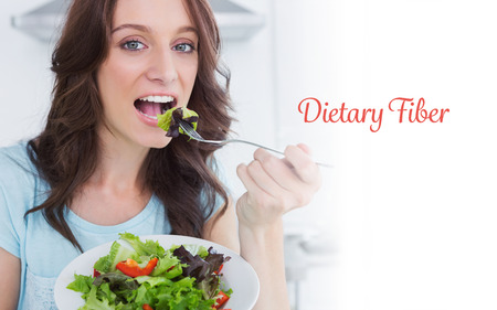 dietary fiber: The word dietary fiber against brunette eating healthy salad