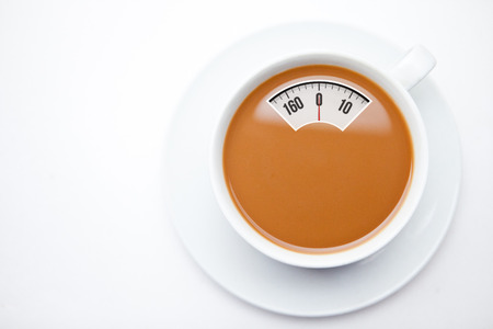 full filled: weighing scales against cup of coffee with milk