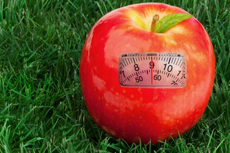 weighing scales: weighing scales against red apple with a leaf on grass Stock Photo